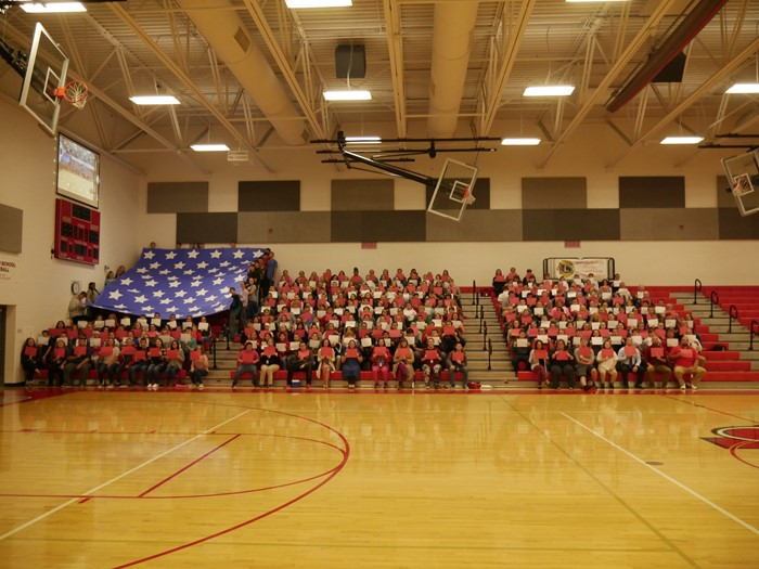 EHS students in staff in the bleachers making an American flag using different colored paper.